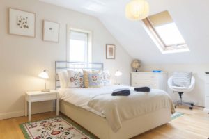 Double bedroom with skylight and chair by My Dublin Vacation boutique townhouses